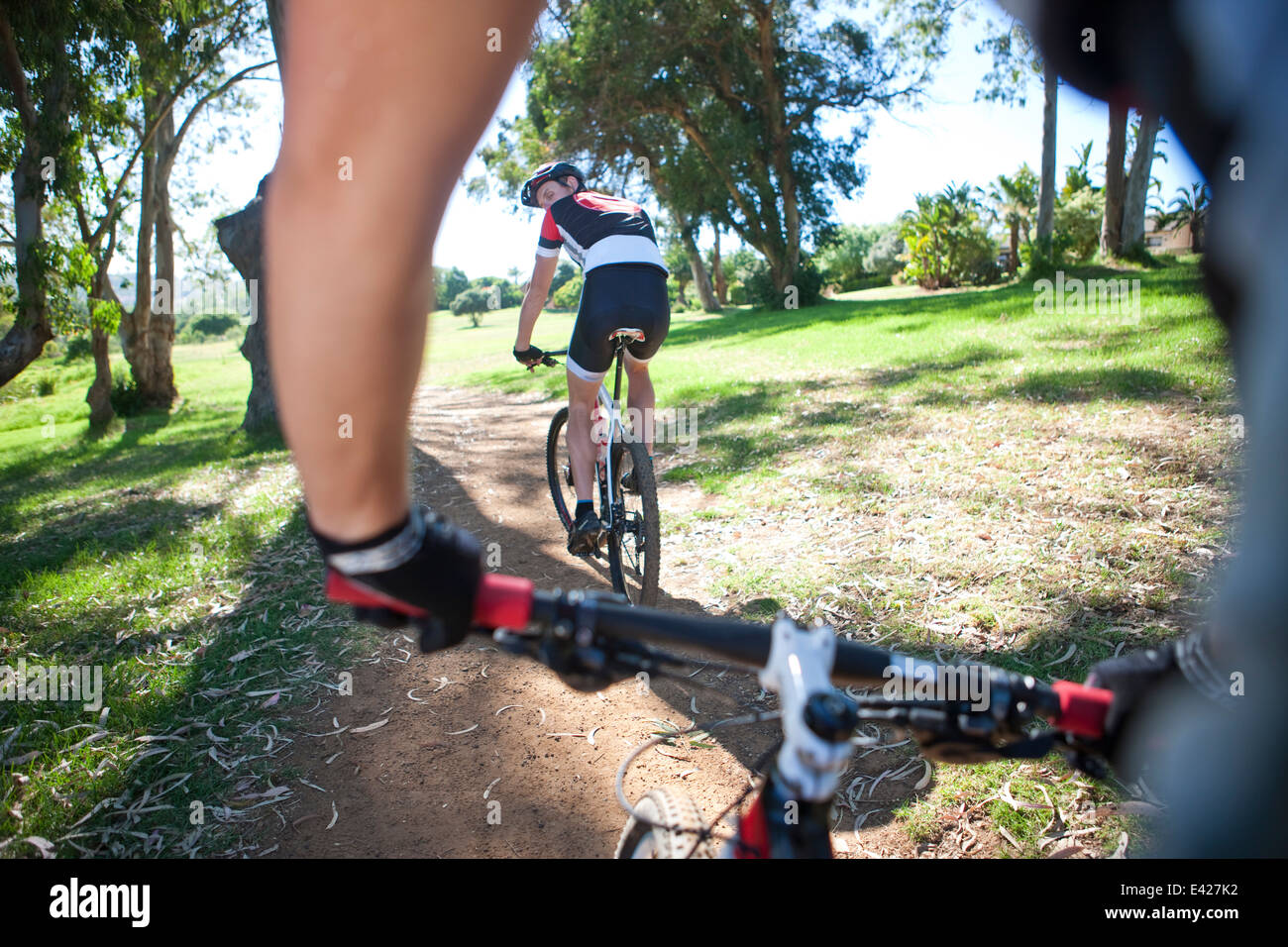 Male cyclist riding ahead of partner - Stock Image