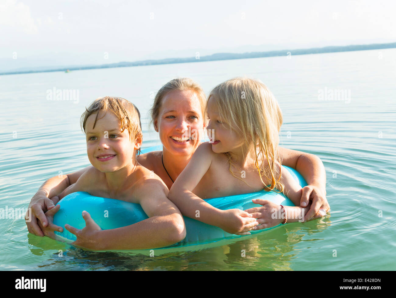 Mother with daughter and son in inflatable ring, Lake Starnberg, Bavaria, Germany - Stock Image