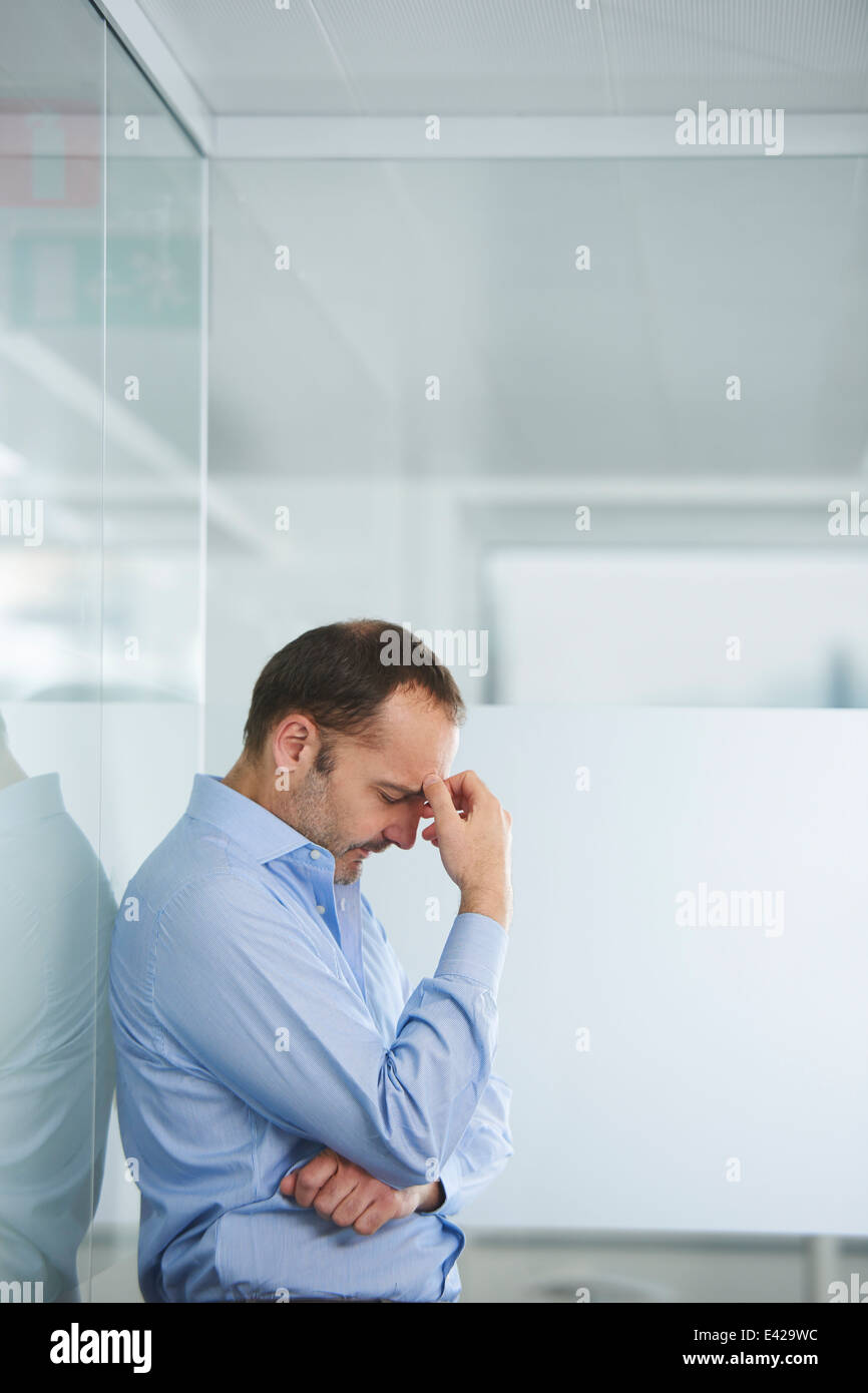 Businessman contemplating against reflective wall - Stock Image