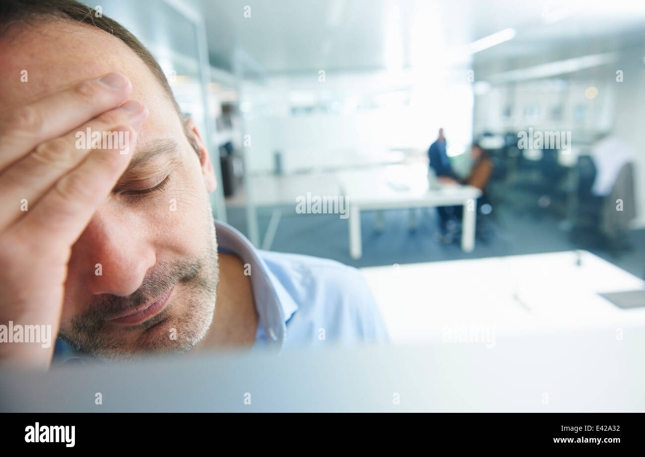 Man thinking, people in background - Stock Image