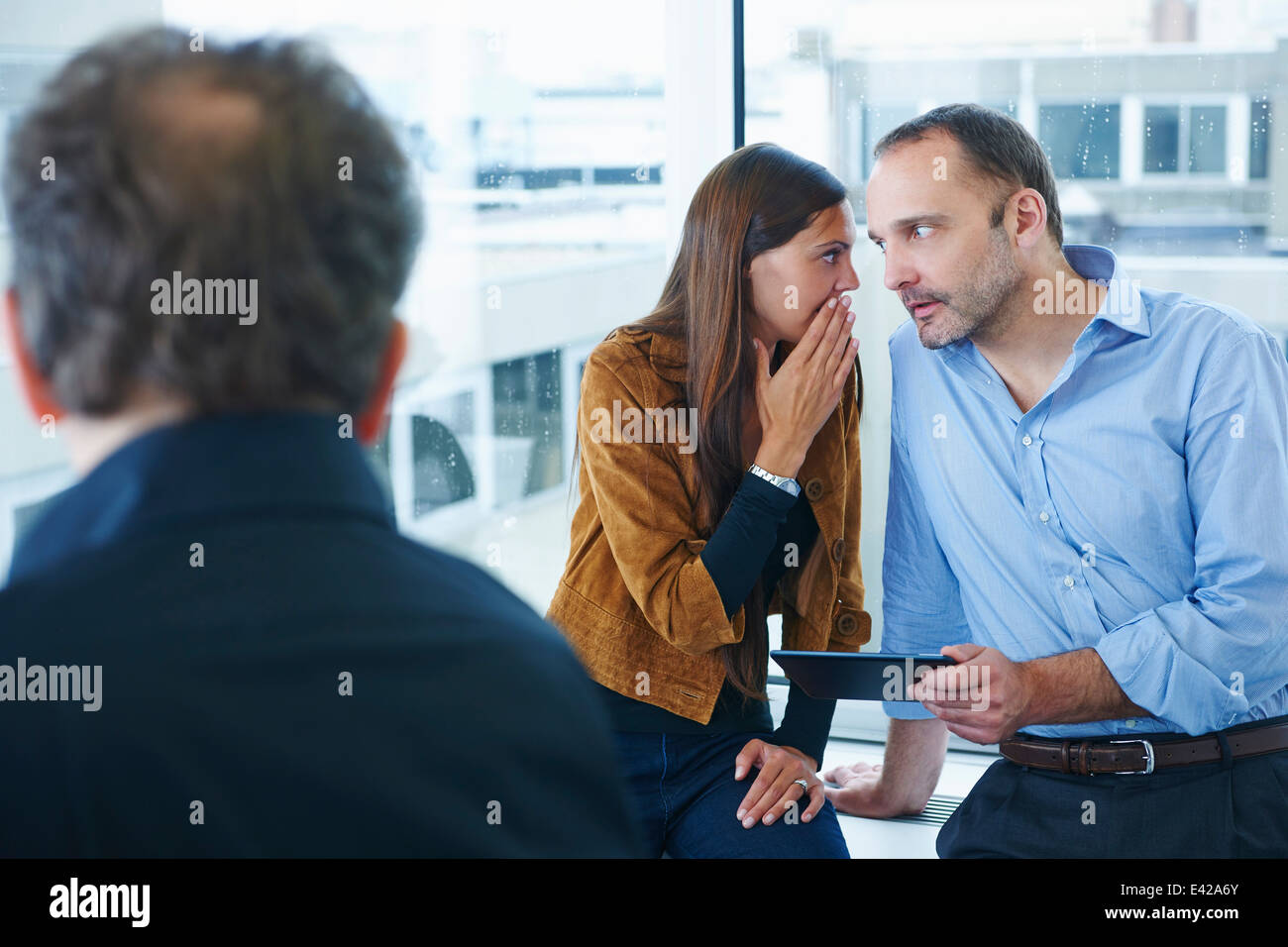 Businesswoman whispering to man in office - Stock Image