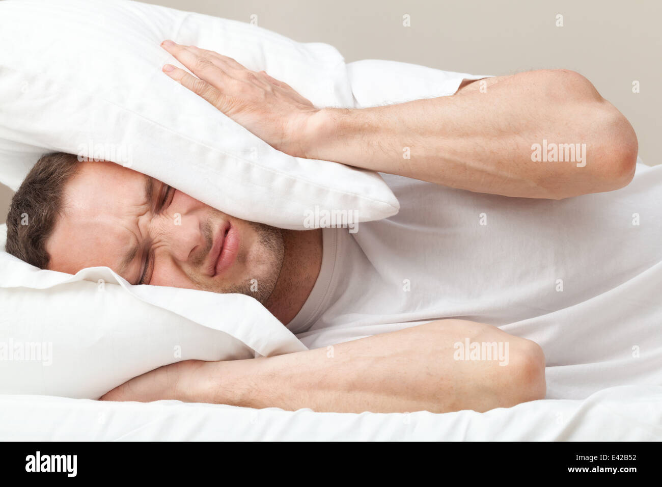 Portrait of dissatisfied Young Caucasian man in bed - Stock Image