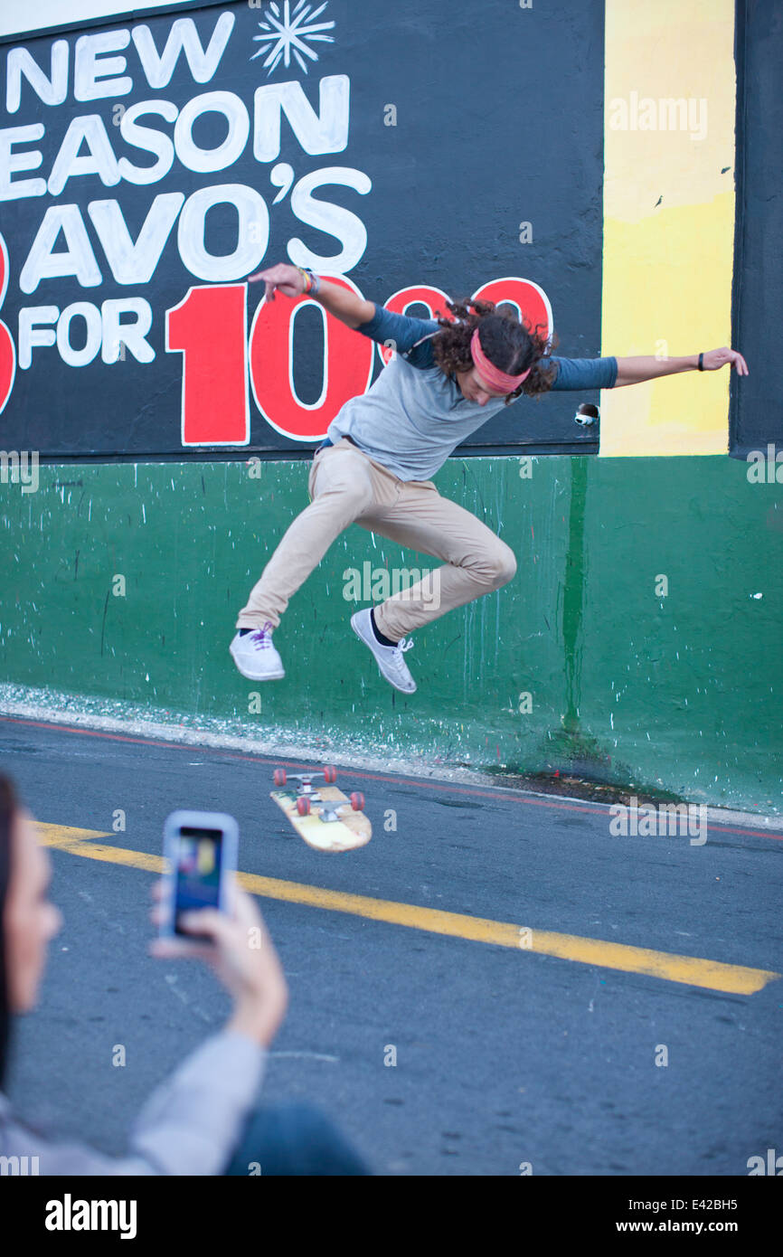 Young adult male being photographed on smartphone doing skateboarding trick - Stock Image