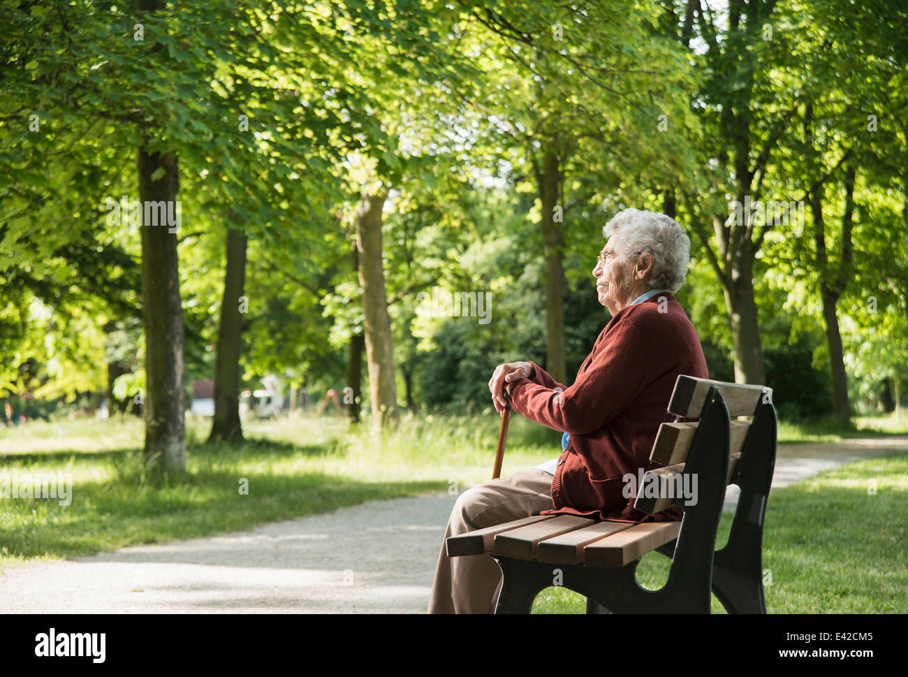 Senior woman sitting on park bench - Stock Image