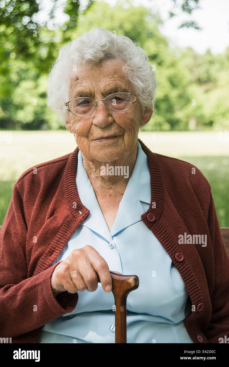 Portrait of senior woman, holding walking stick - Stock Image