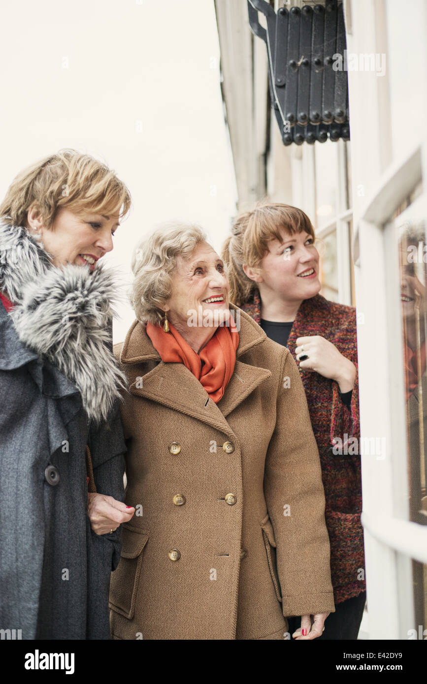 Senior woman with daughter and granddaughter, looking in window Stock Photo