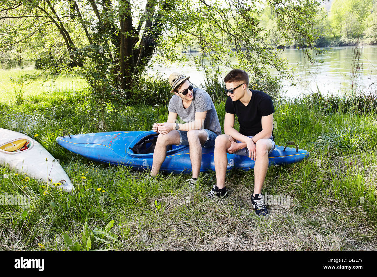 Two young men sitting on a canoe - Stock Image