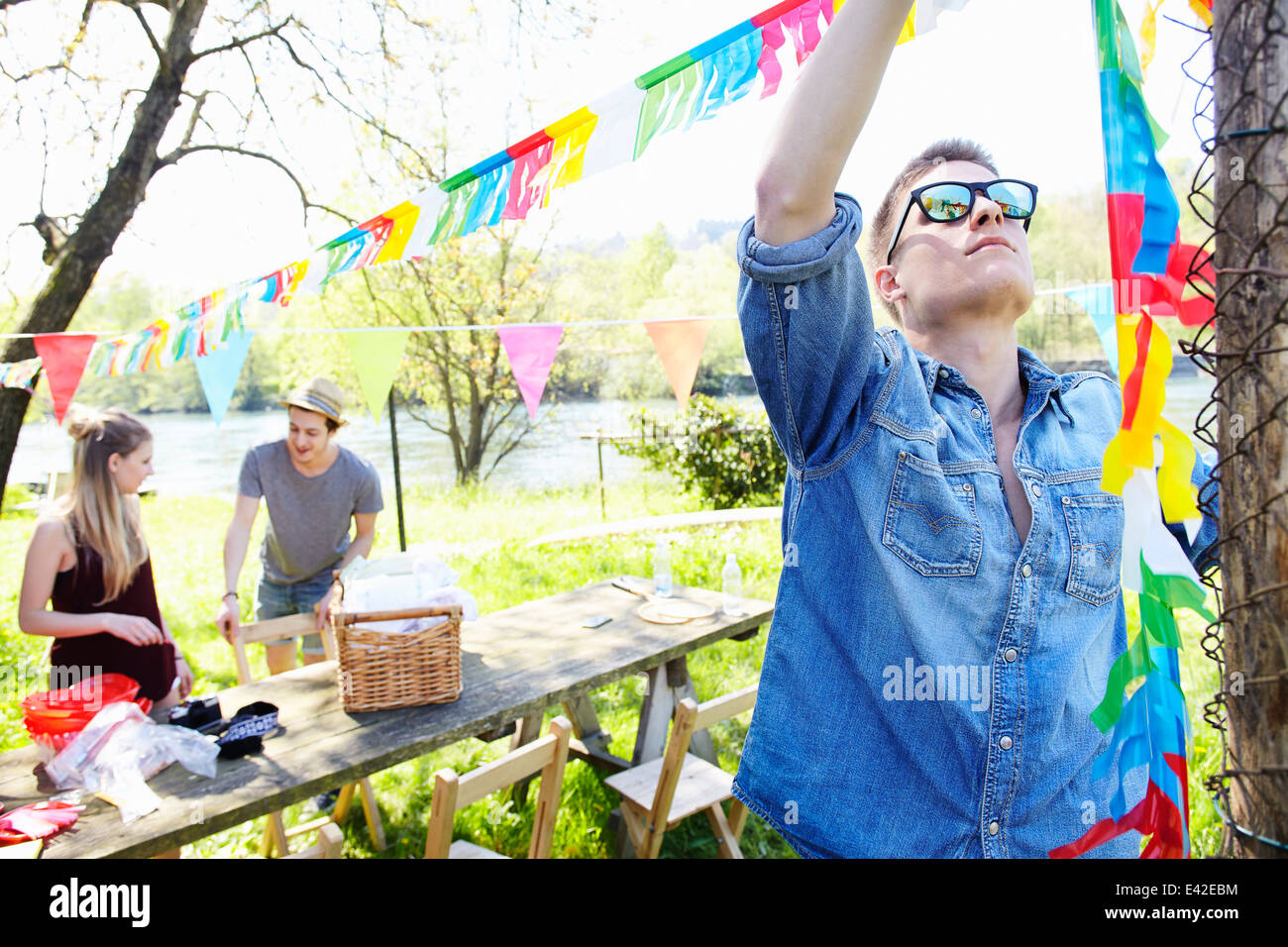 Young man hanging up bunting - Stock Image