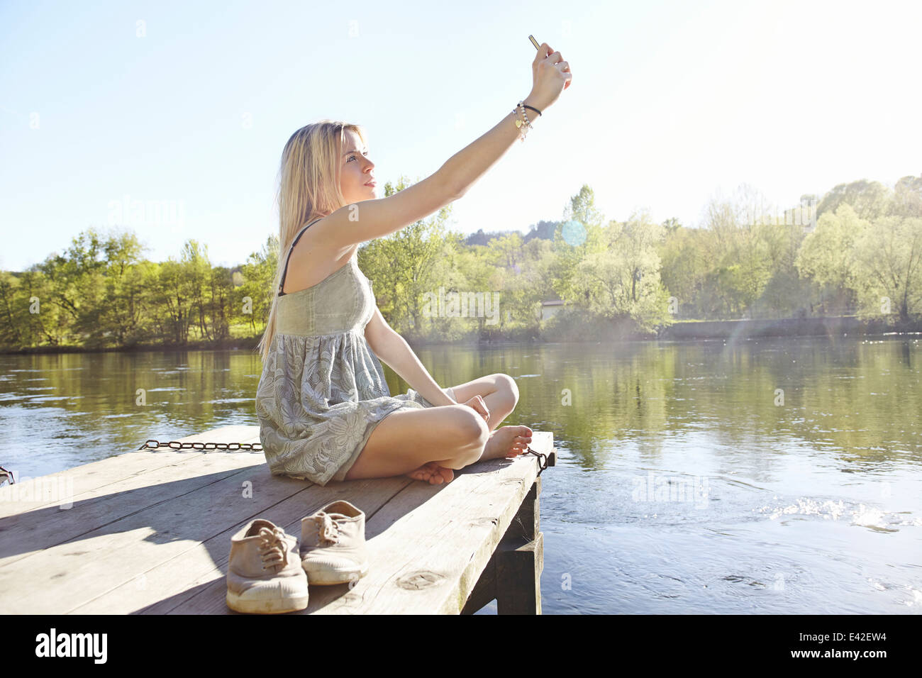 Young woman sitting on jetty photographing herself - Stock Image