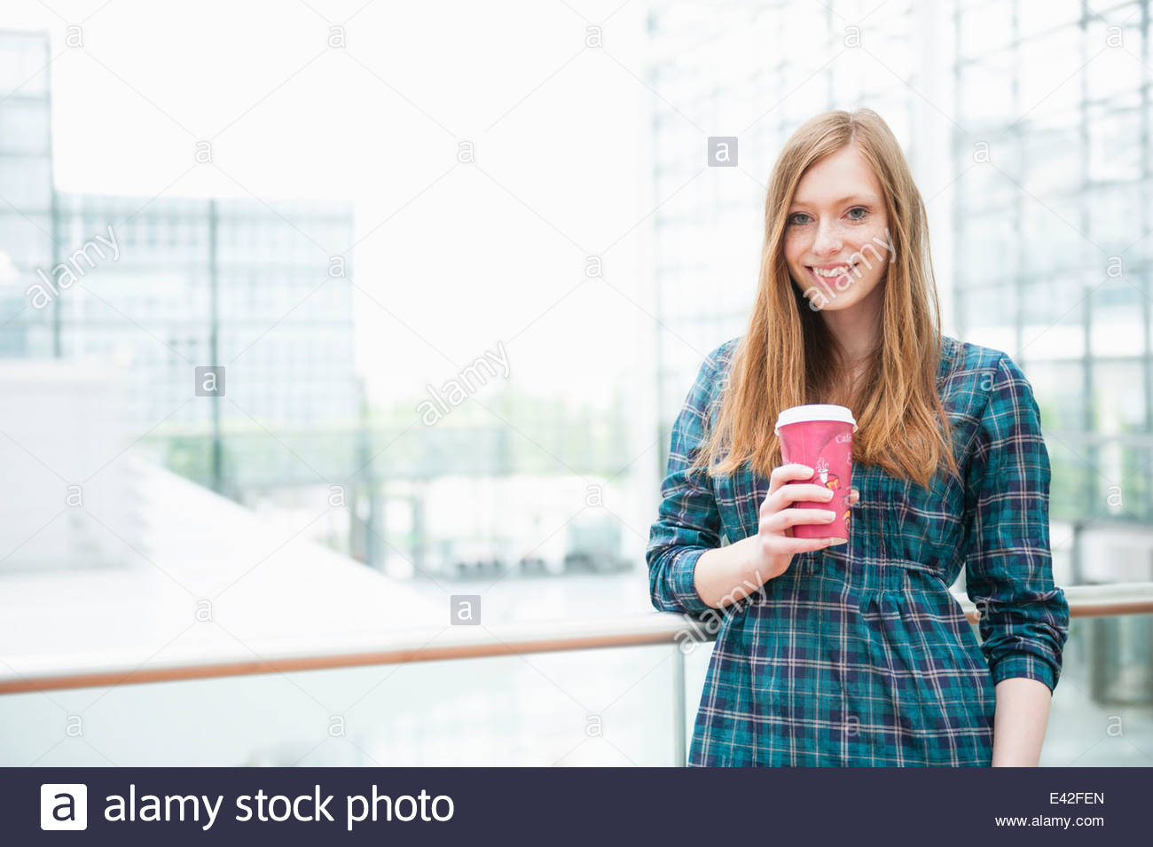 Portrait of young woman in city with takeaway coffee - Stock Image