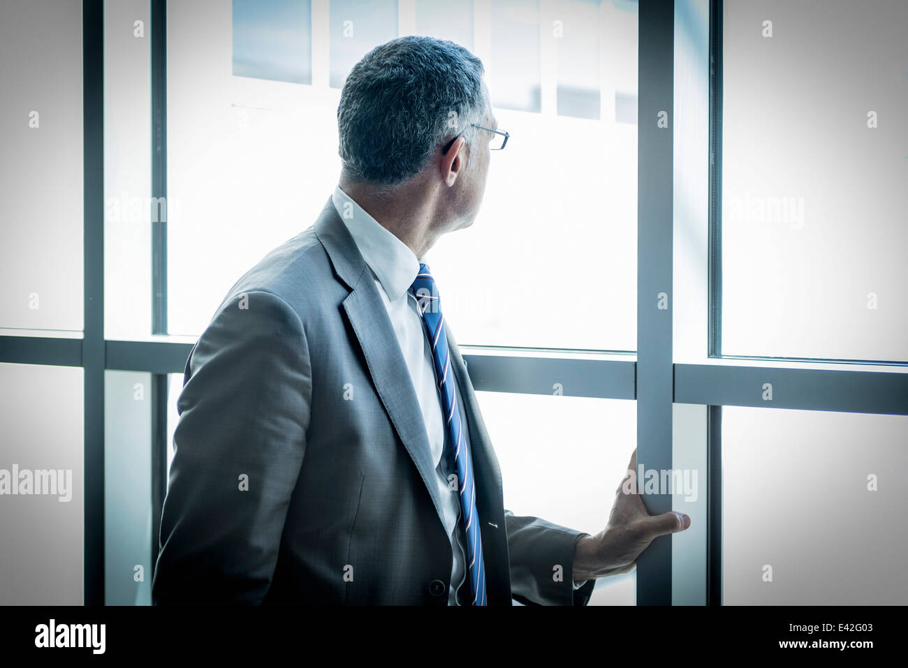 Businessman looking out through glass wall - Stock Image