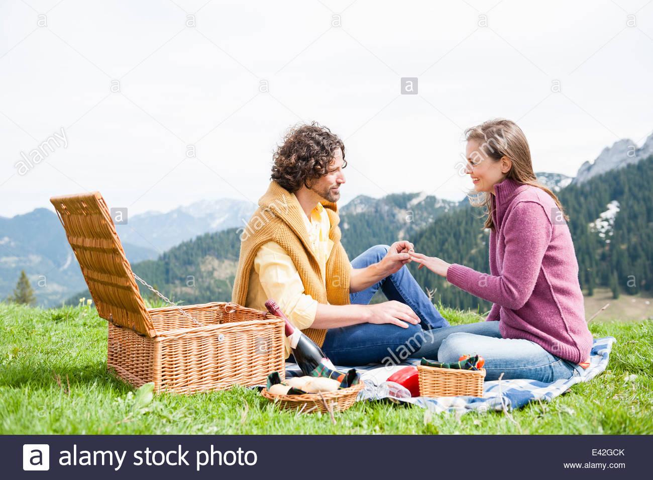 Romantic mid adult couple having engagement picnic, Wallberg, Tegernsee, Bavaria, Germany - Stock Image