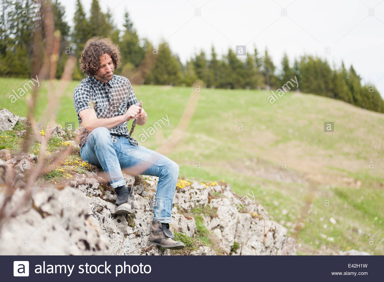 Mid adult man carving a stick with penknife, Wallberg, Tegernsee, Bavaria, Germany - Stock Image