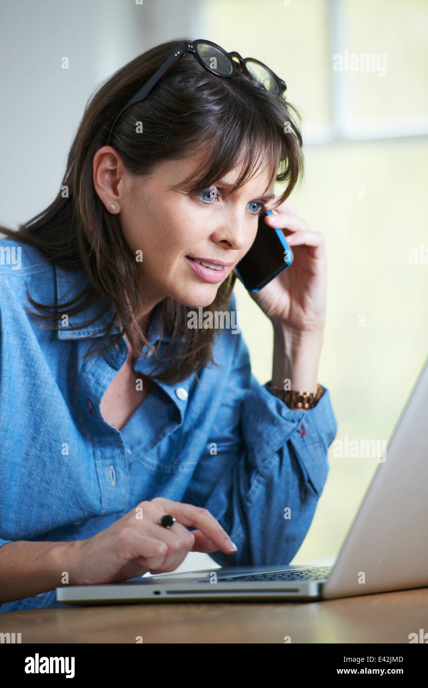 Mature woman on phonecall and using smartphone - Stock Image