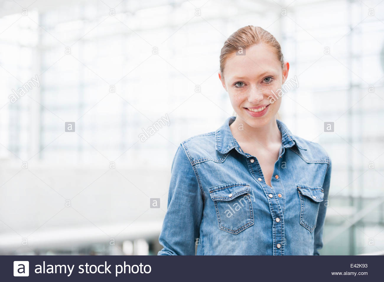 Portrait of shy young city woman - Stock Image