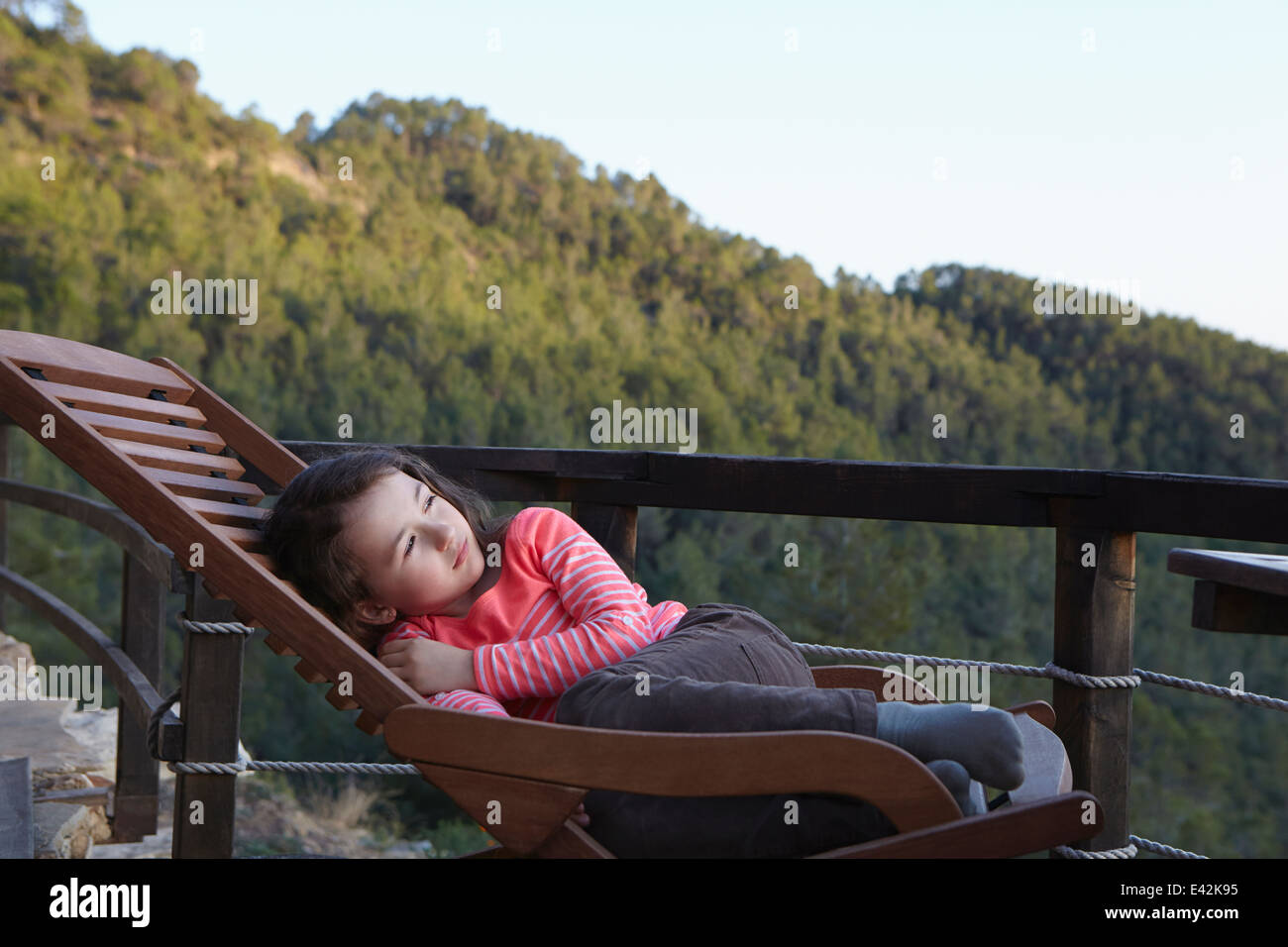 Young girl curled up on balcony deckchair gazing upward - Stock Image