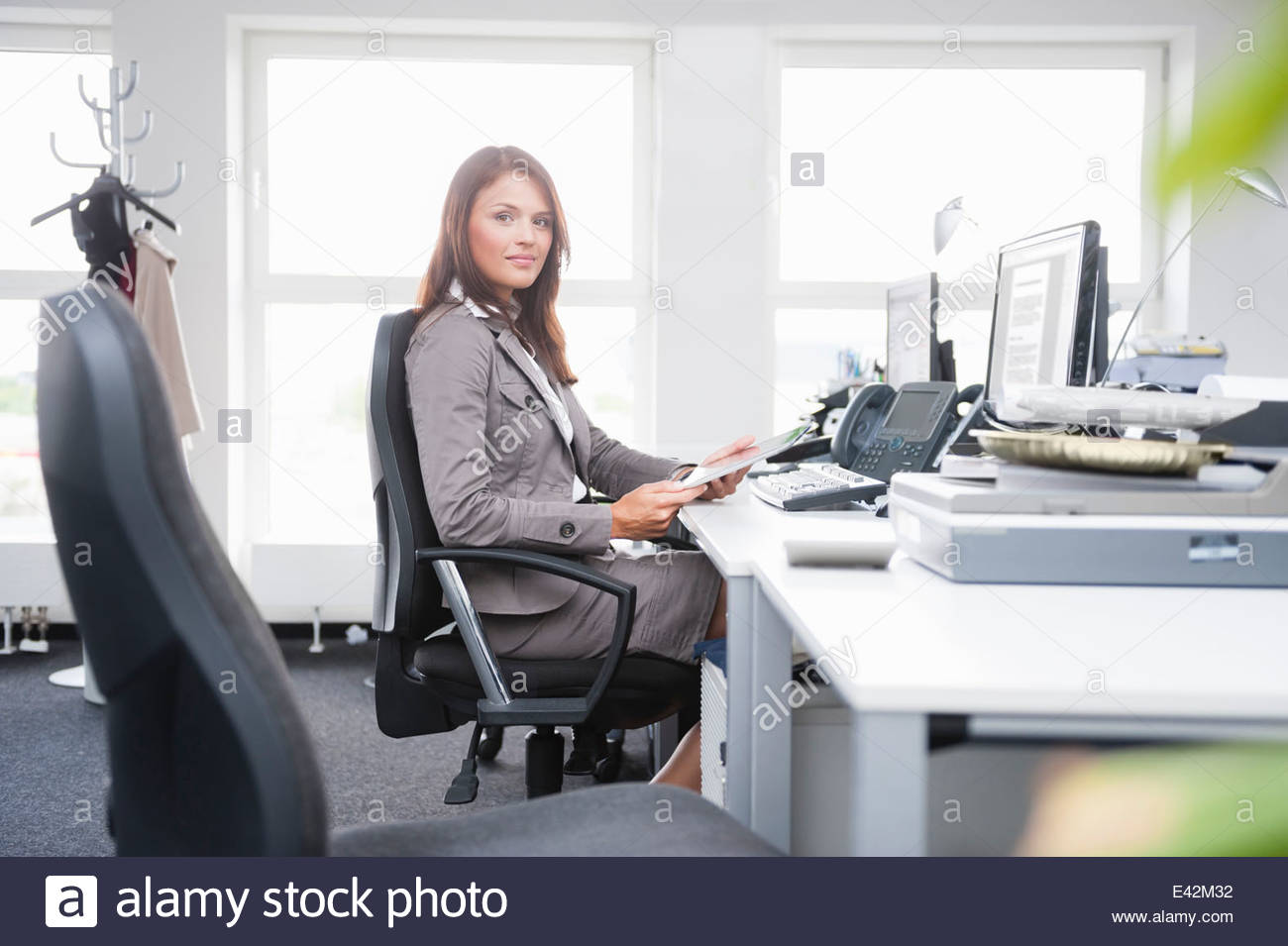 Mid adult woman sitting at desk - Stock Image