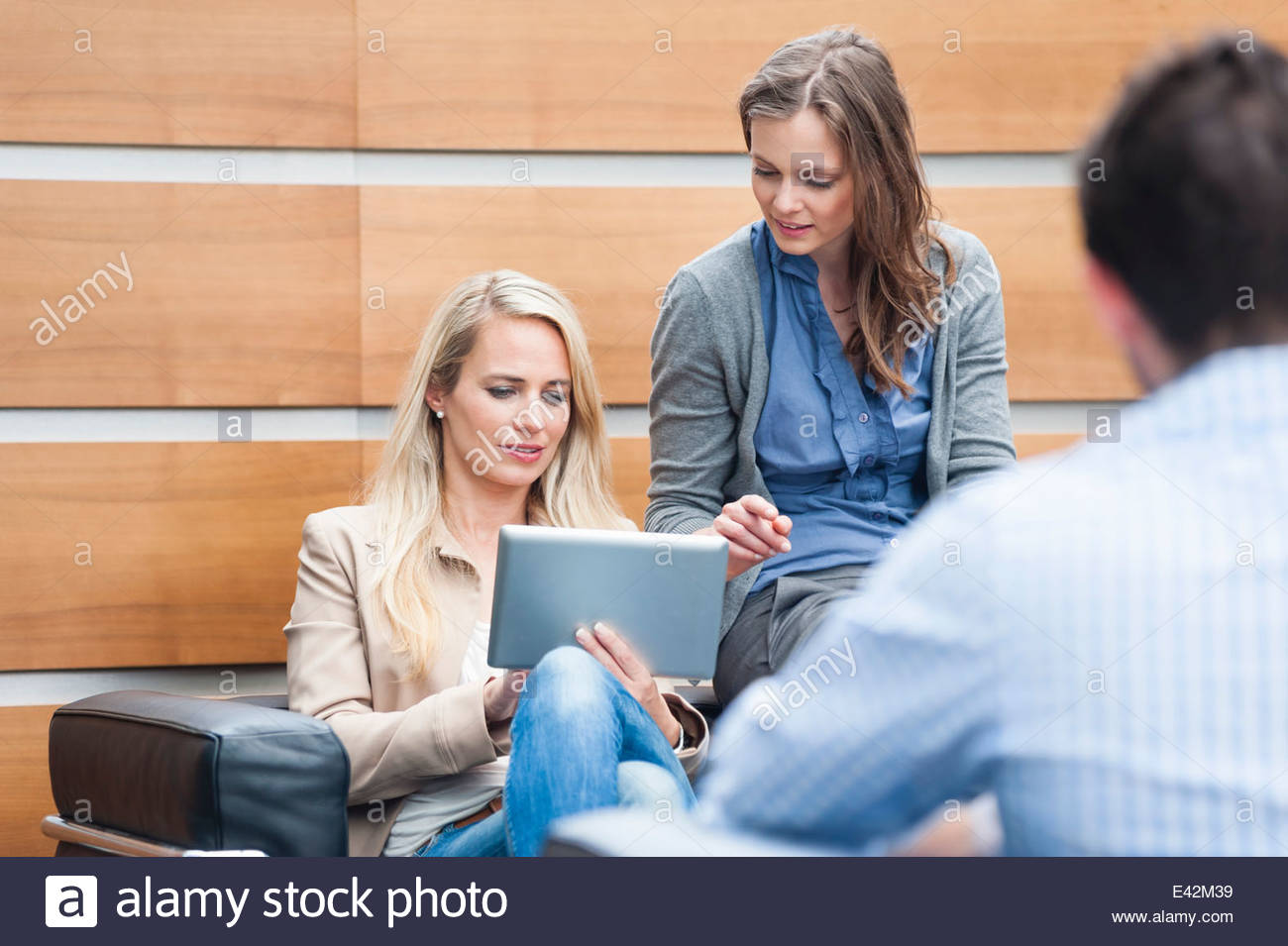 Business colleagues using digital tablet - Stock Image
