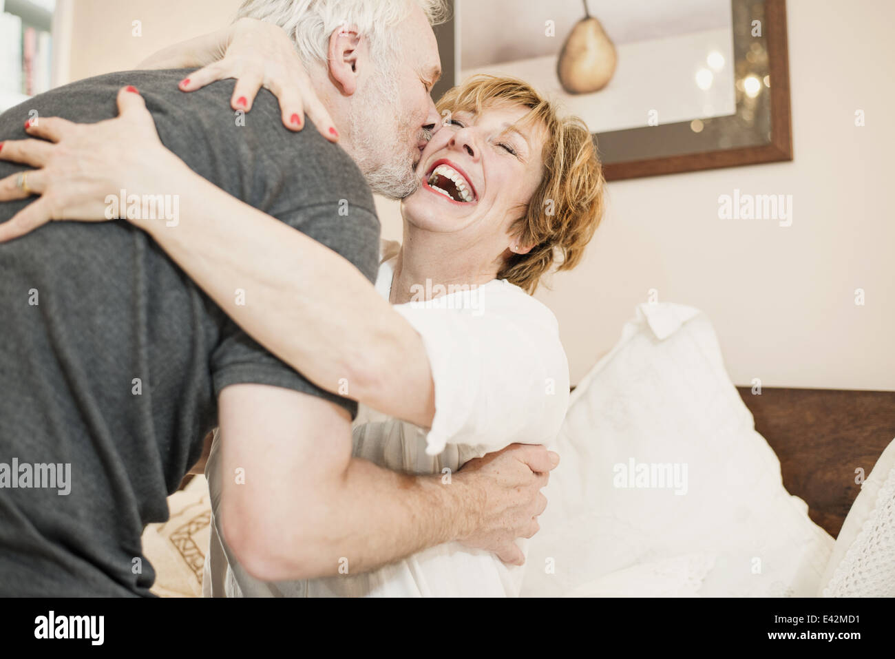 Couple hugging, mature woman laughing Stock Photo