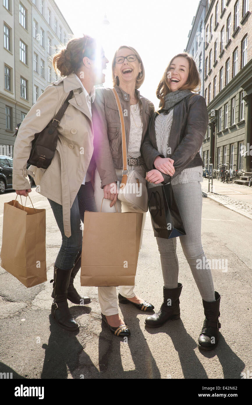 Three generation females with shopping bags on city street - Stock Image