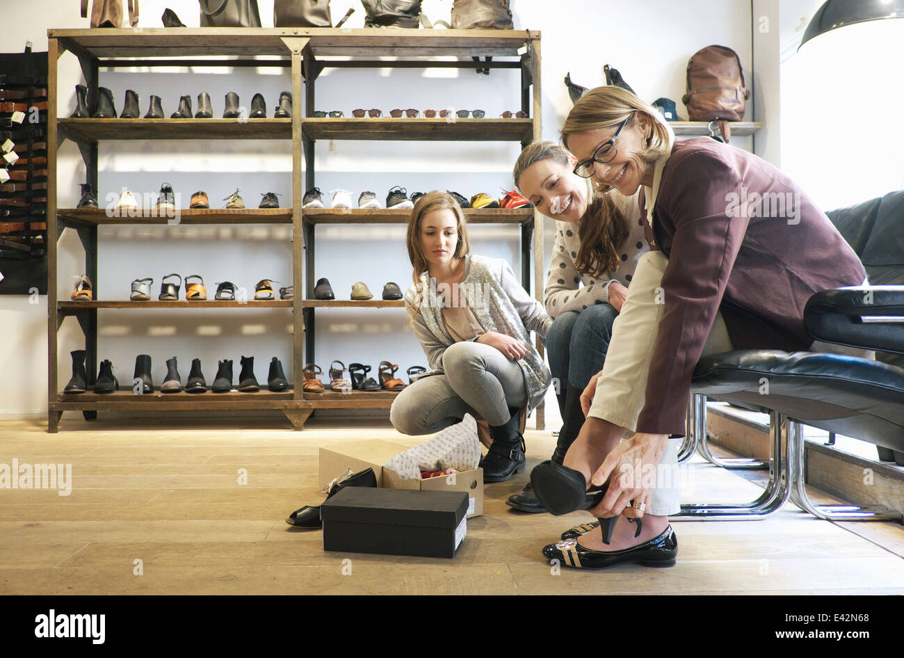 Three generation females trying out shoes in shoe shop - Stock Image