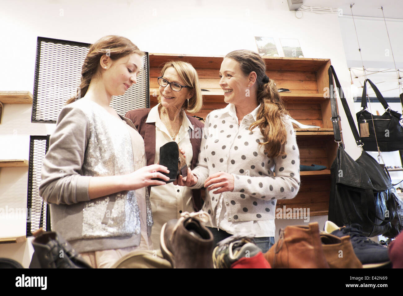 Three generation females looking at ankle boot in shoe shop - Stock Image