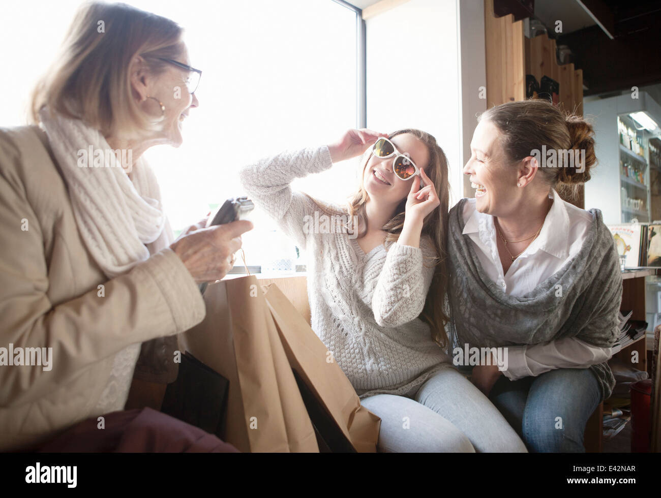 Three generation females trying on sunglasses in shop - Stock Image