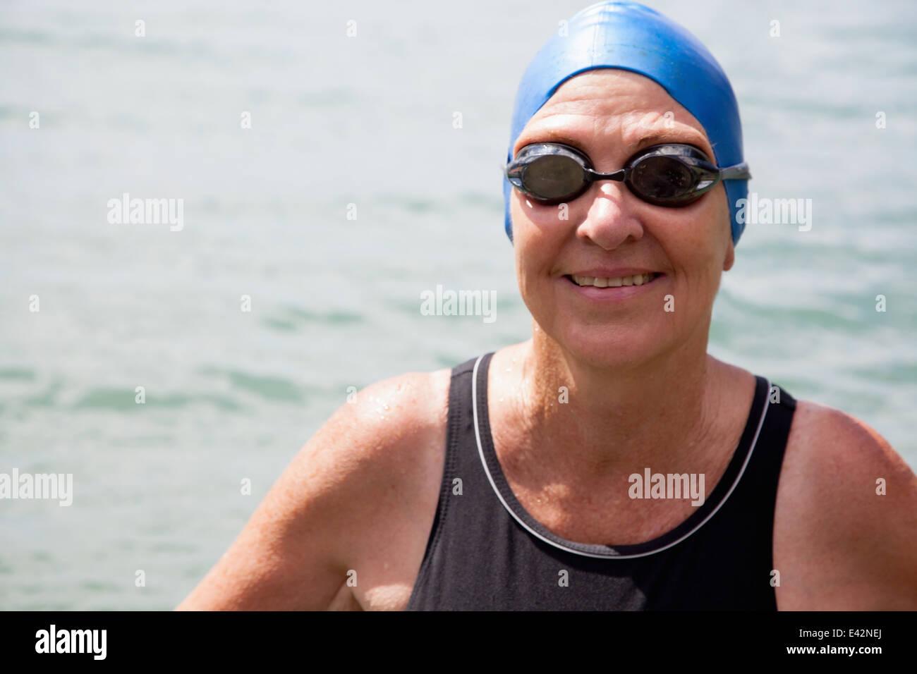 Close up portrait of senior woman swimmer in sea - Stock Image