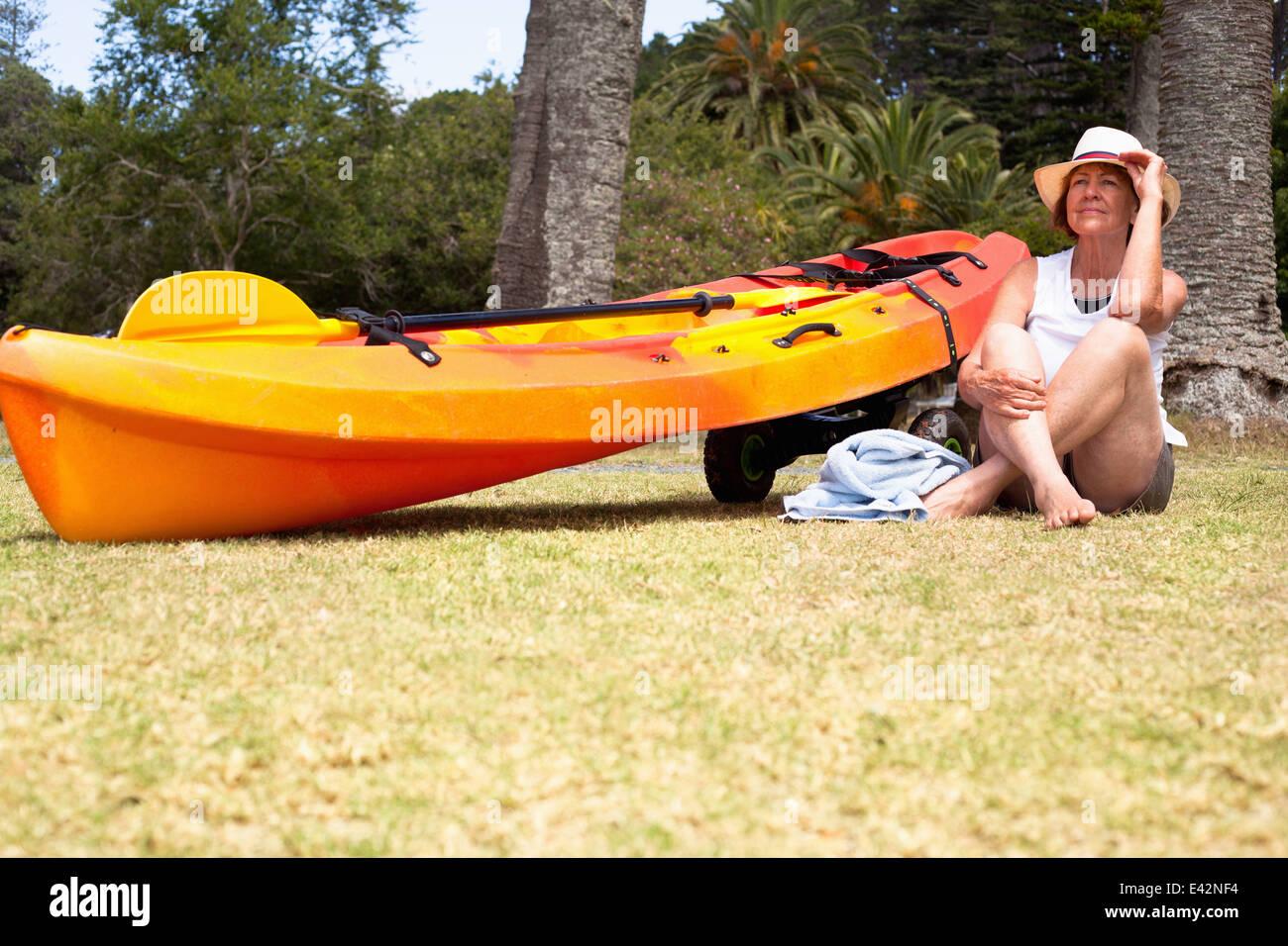 Senior woman sitting cross legged on beach Stock Photo