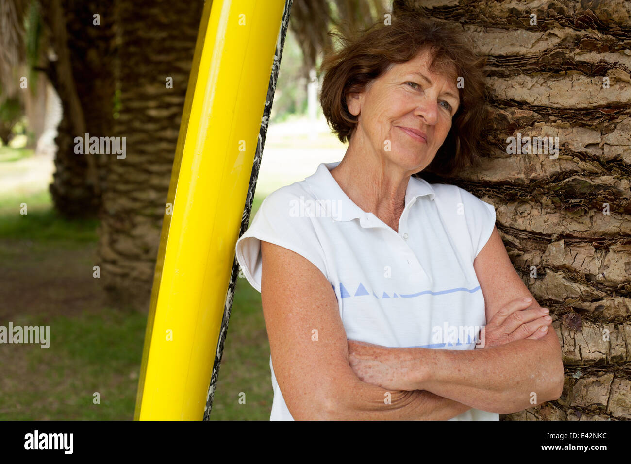 Portrait of senior woman leaning against palm tree in park - Stock Image