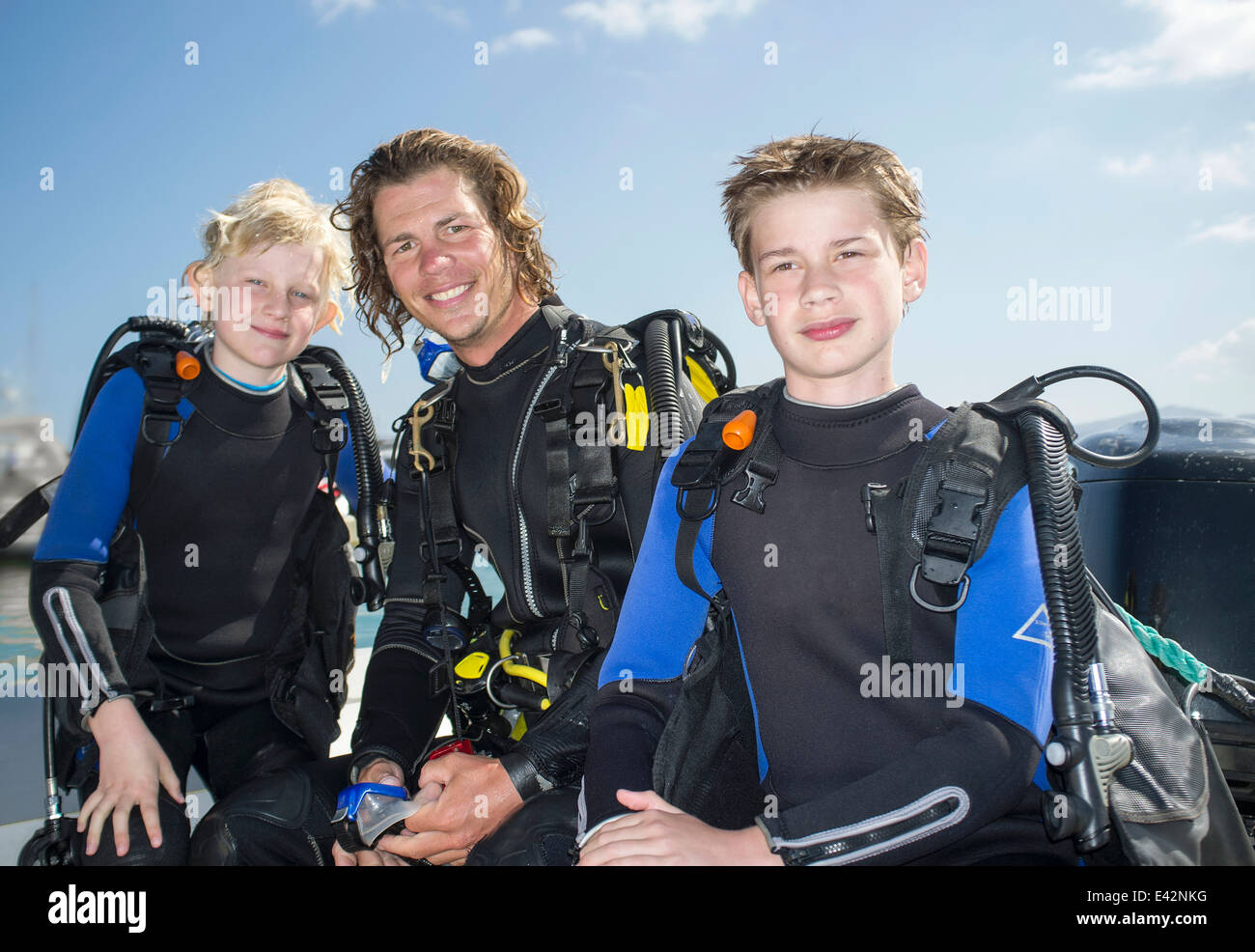 Portrait of two boys with mid adult male scuba diving teacher - Stock Image
