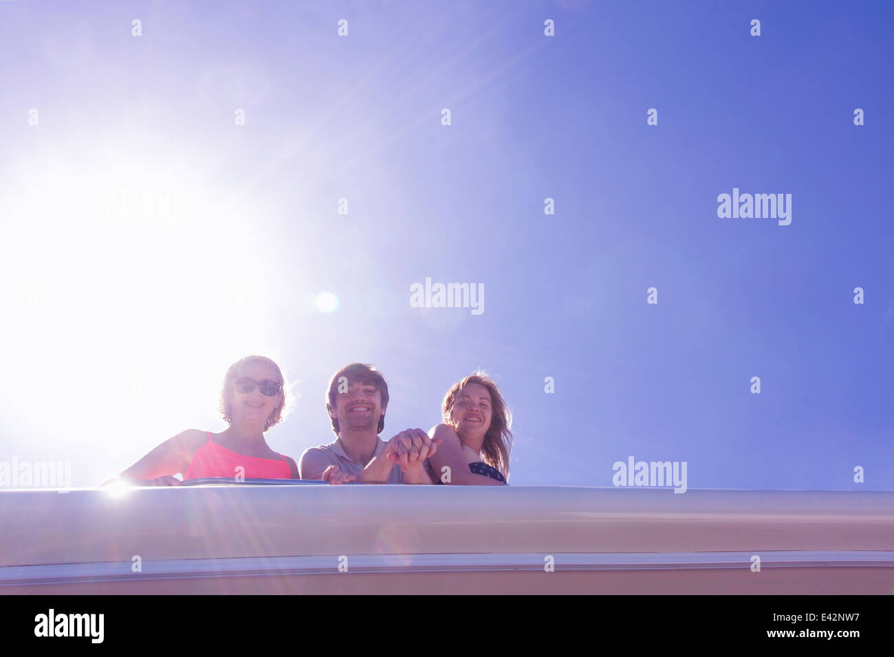 Portrait of three adult friends looking down from yacht - Stock Image