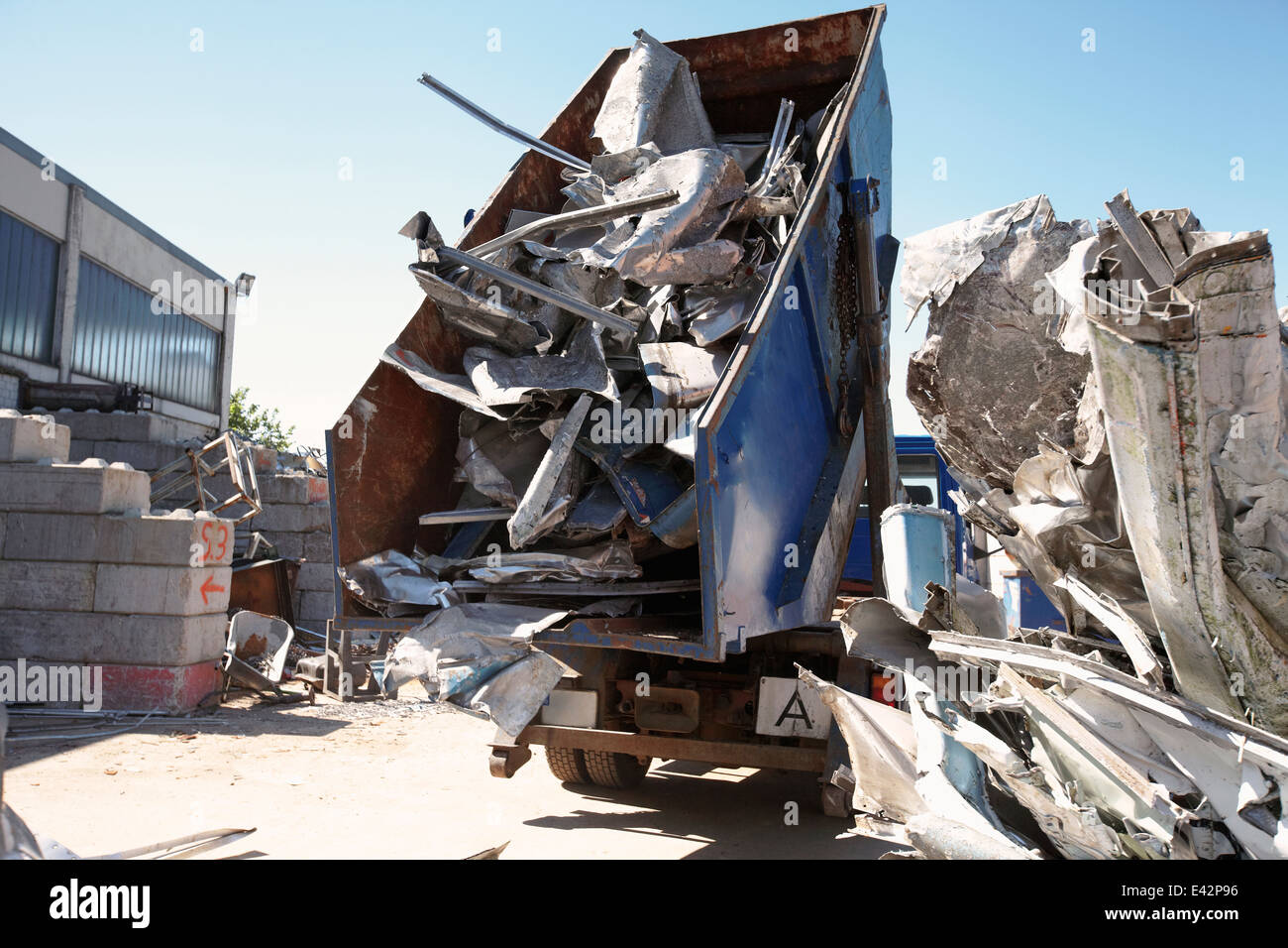 Dump truck emptying aluminium from skip into scrap yard - Stock Image