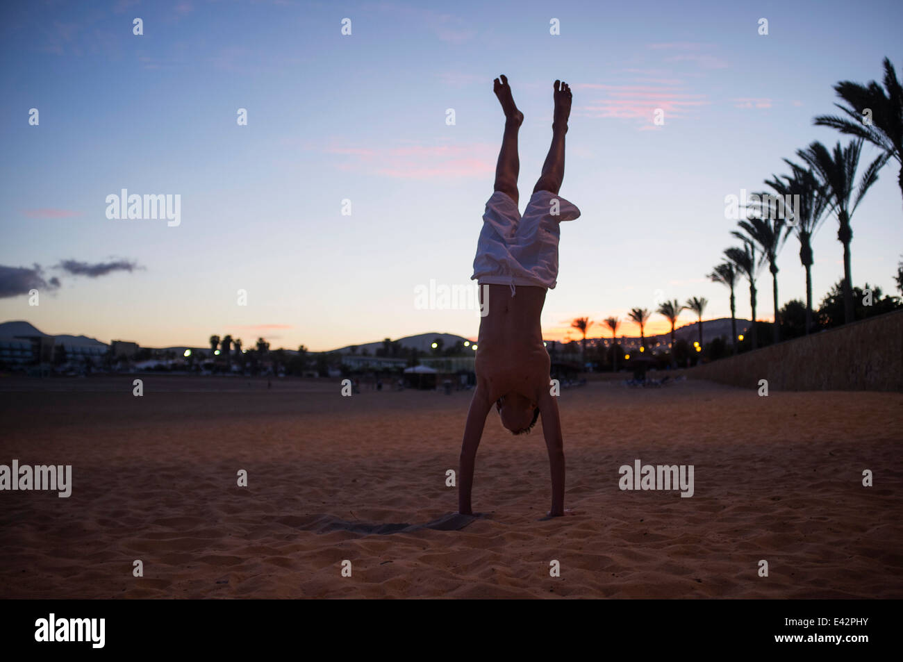 Silhouetted boy doing handstand on beach at dusk - Stock Image
