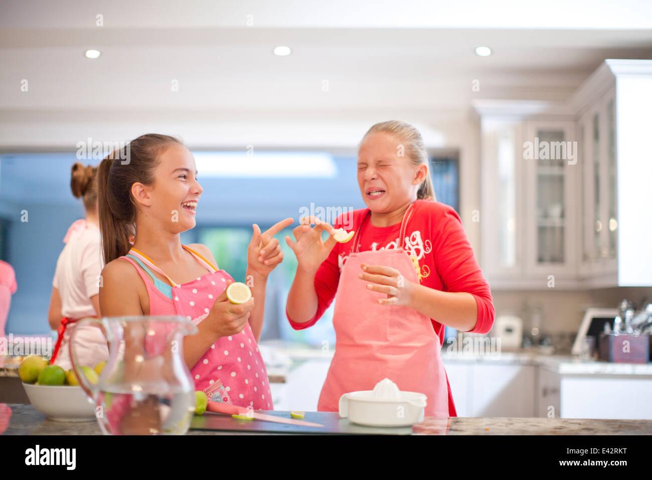 Two teenage girls tasting sour lemons in kitchen - Stock Image