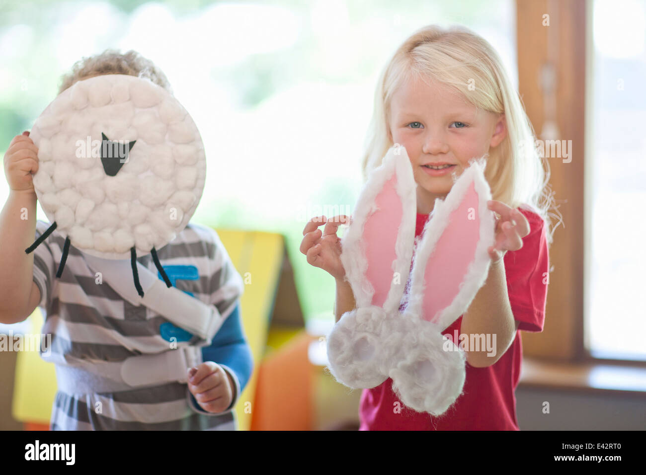 Boy and girl holding up sheep and rabbit creations at nursery school - Stock Image
