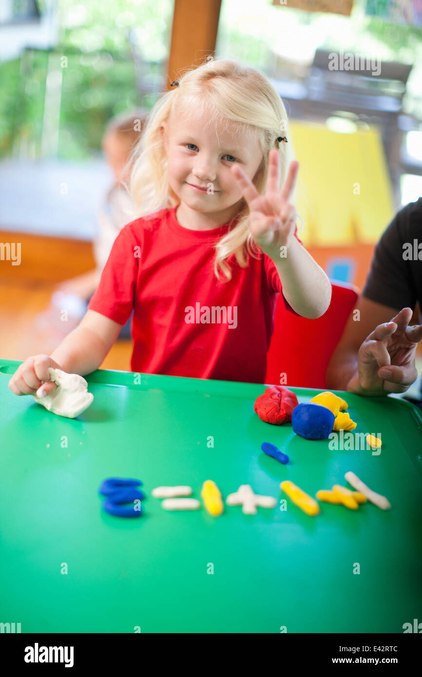 Portrait of girl counting with fingers at nursery school - Stock Image