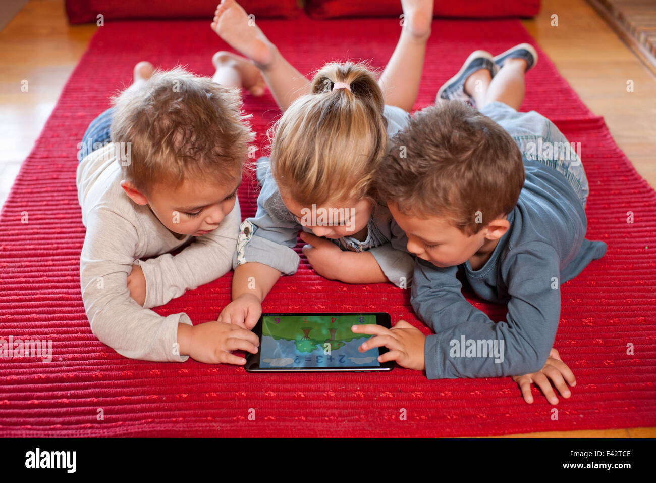 Boys and a girl using digital tablet at nursery school Stock Photo