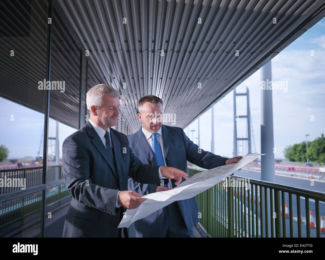 Civil engineering architects inspecting plans of suspension bridge. The Humber Bridge, UK, built in 1981 - Stock Image