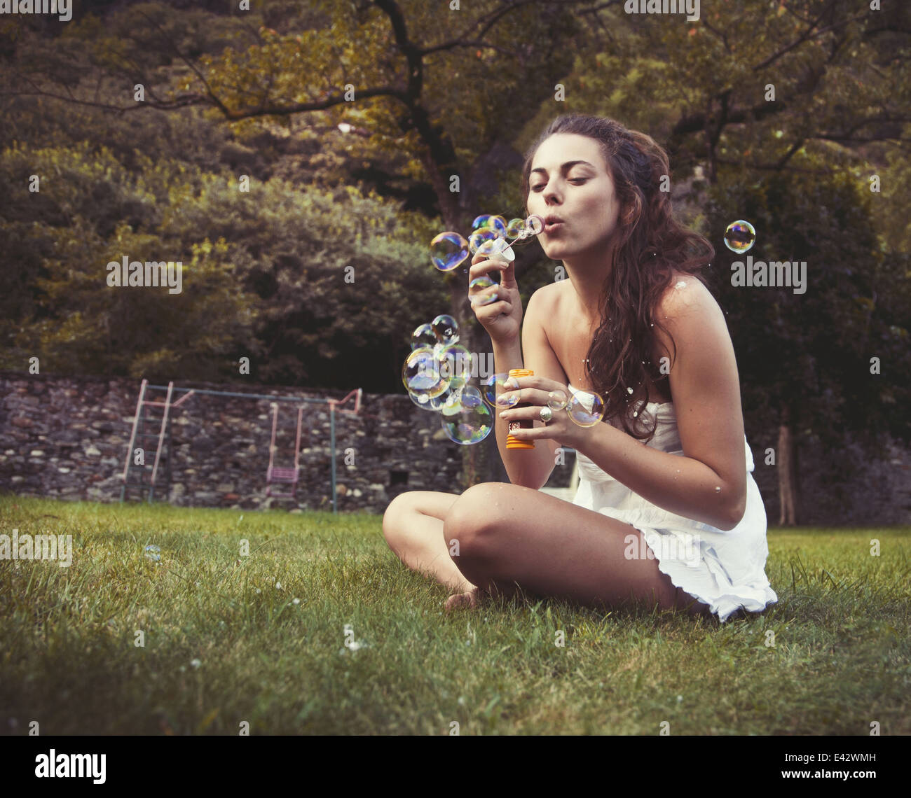 Young woman sitting in field blowing bubbles - Stock Image