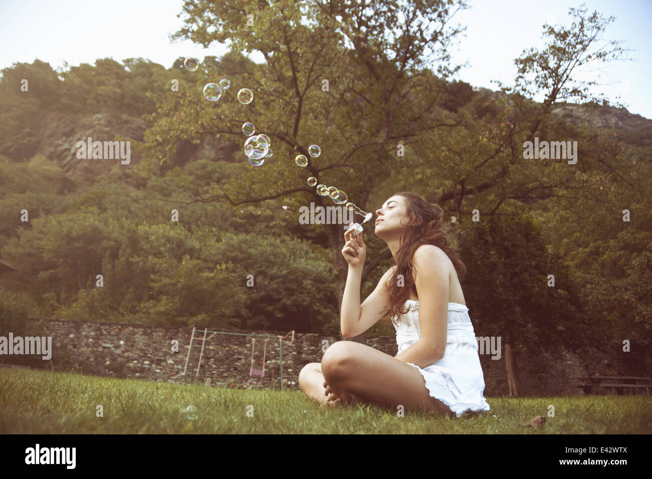 Young woman sitting cross legged in field blowing bubbles - Stock Image