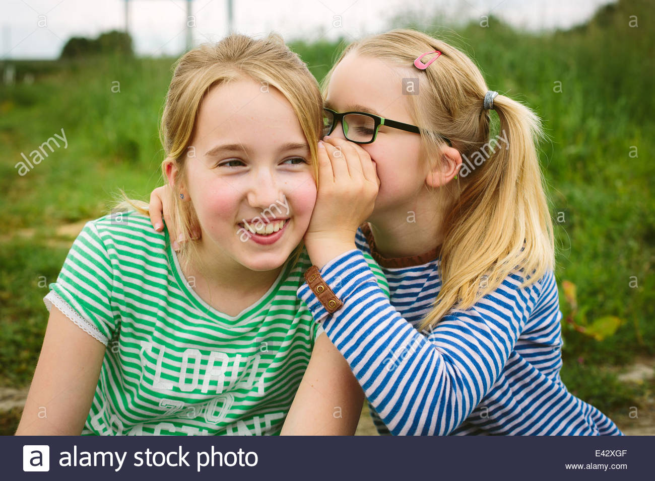 Nine year old girl whispering to sister in field - Stock Image