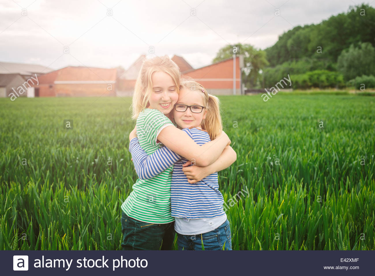 Portrait of nine year old girl and sister hugging in field - Stock Image