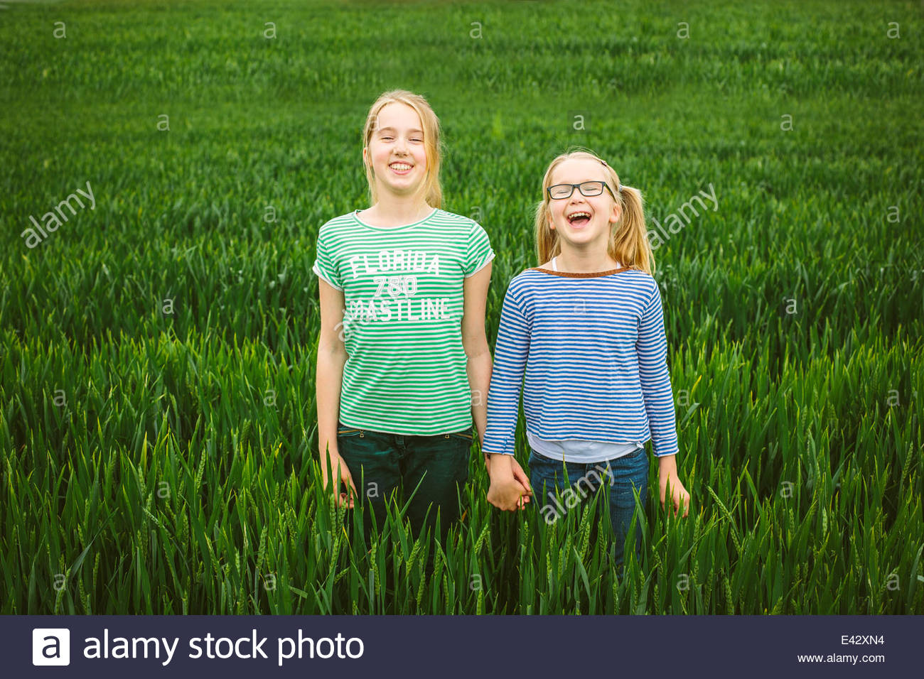 Portrait of nine year old girl and sister holding hands in field - Stock Image