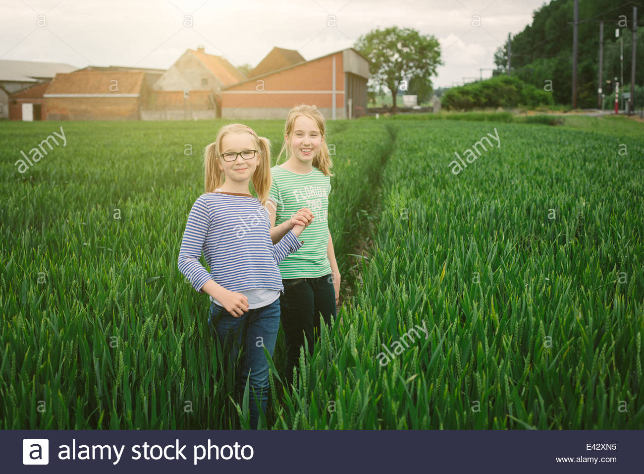 Portrait of nine year old girl and sister on field path - Stock Image