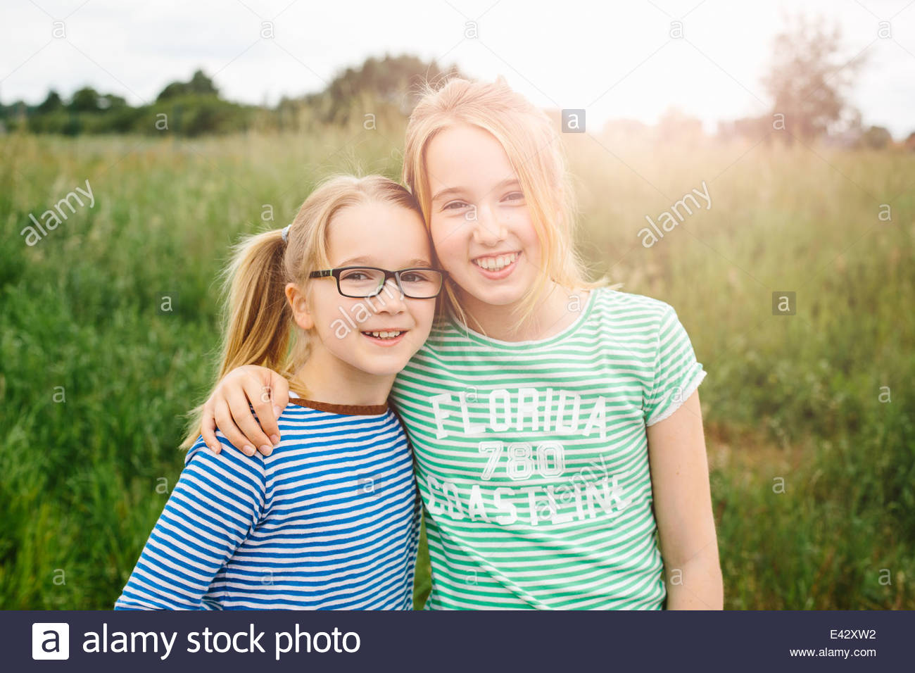 Portrait of eleven year old girl hugging sister in field - Stock Image