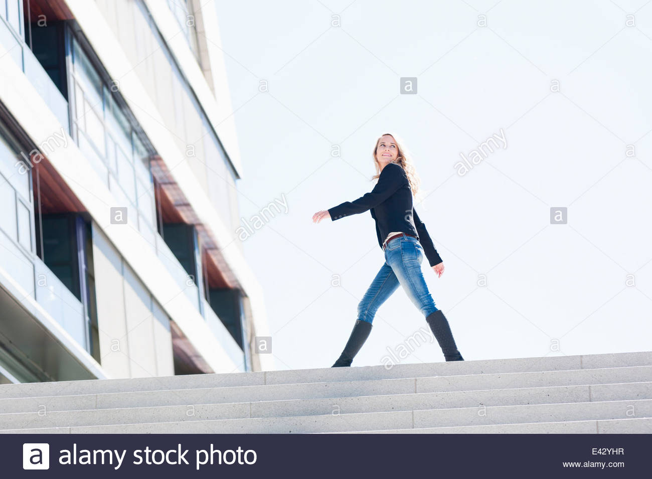 Mid adult woman striding toward office building in city - Stock Image