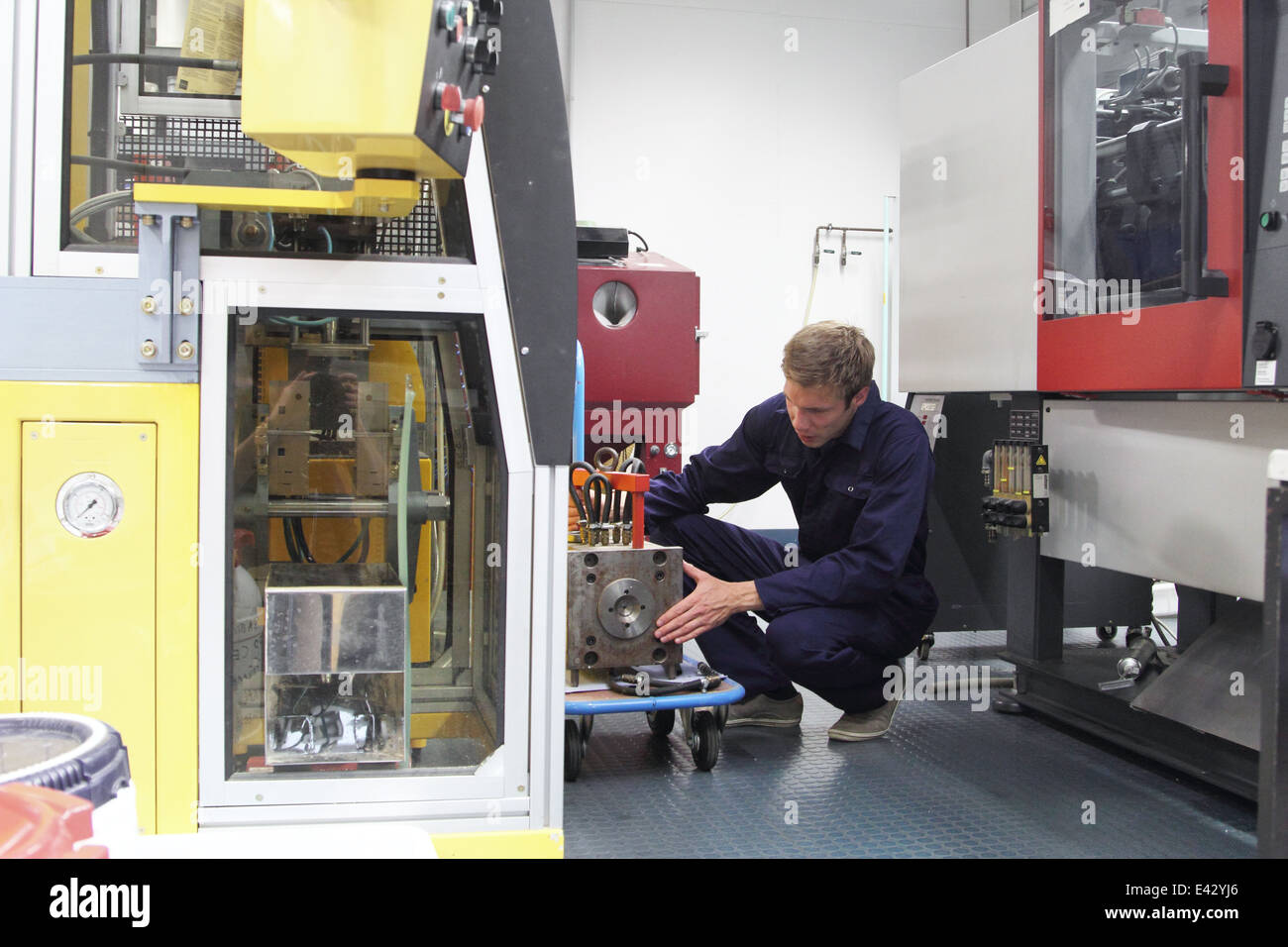 Male engineer repairing manufacturing machine in factory - Stock Image