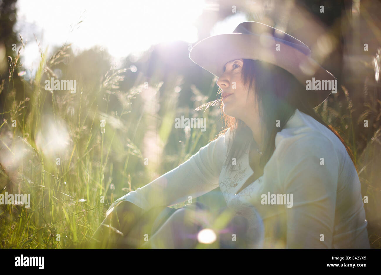 Mature woman in cowboy hat with blade of grass in her mouth - Stock Image