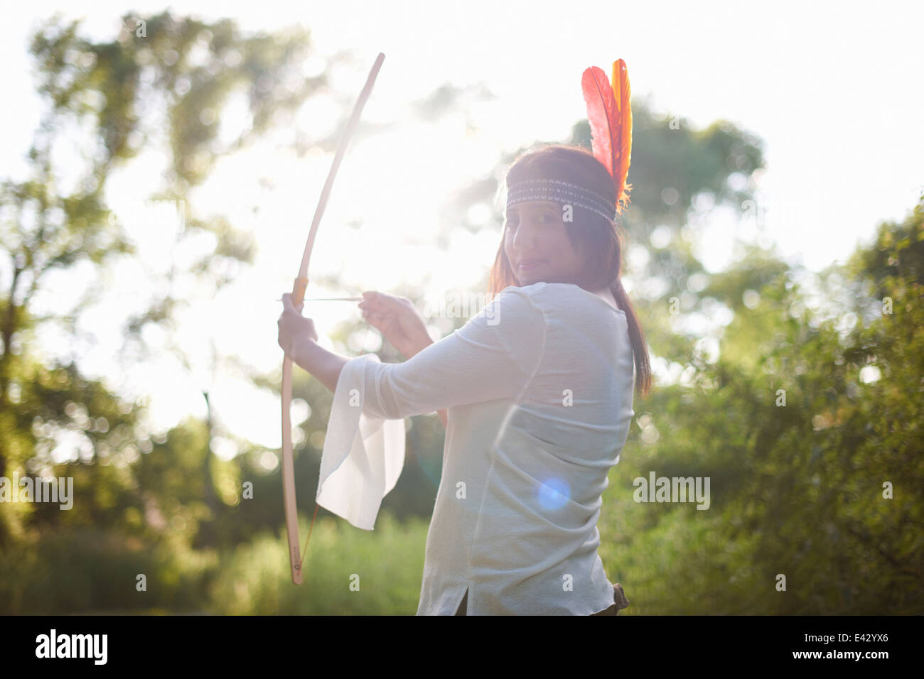 Portrait of mature woman in woodlands aiming bow and arrow - Stock Image
